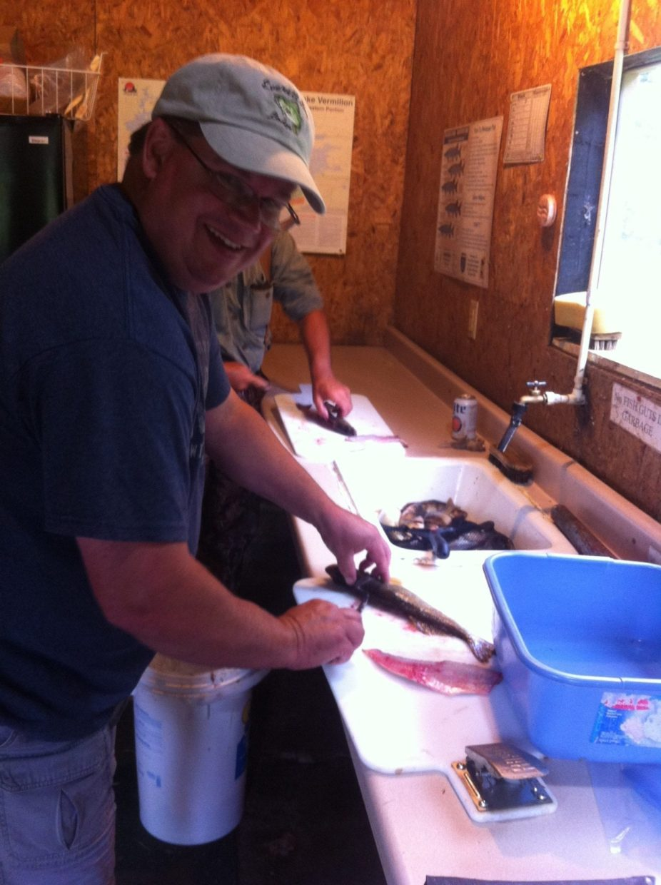 man helping Cliff Wagenbach clean fish