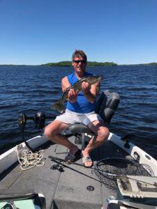 Man sitting in boat holding walleye